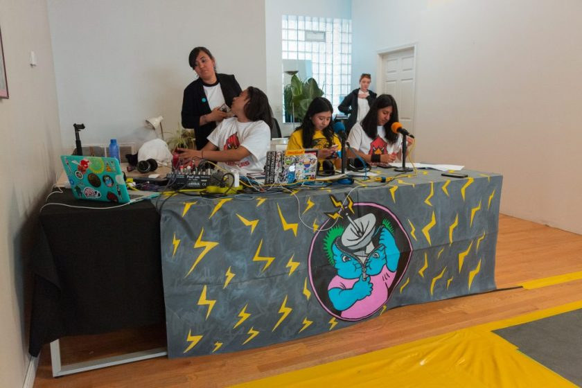 "Image: In-Session, at Threewalls in June 2018, by El Cardenal De Aztlán and collaborators, in response to the guiding work ""Borderlands/La Frontera"" by Gloria Anzaldúa. Three artists sit behind a long table in the foreground and two stand behind them, one near, one farther back. On the table is a detailed dark grey covering (illustrated with yellow z-shapes like lightning bolts, as well as a circular inset showing a blue character unzipping its head open to reveal an active broadcast dish) and on that sit two microphones, two laptops, a soundboard, and other pieces of technology. The two artists seated behind the microphones each wear a t-shirt that matches the off-camera performers (a yellow t-shirt with a jaguar or a white t-shirt with a cardinal) and look down. The third artist wears the cardinal t-shirt and sits behind a soundboard, twisting back to talk to a person behind them. A yellow section of floor is visible in the lower-right corner of the frame. Photo by Milo Bosh. Courtesy of Threewalls."