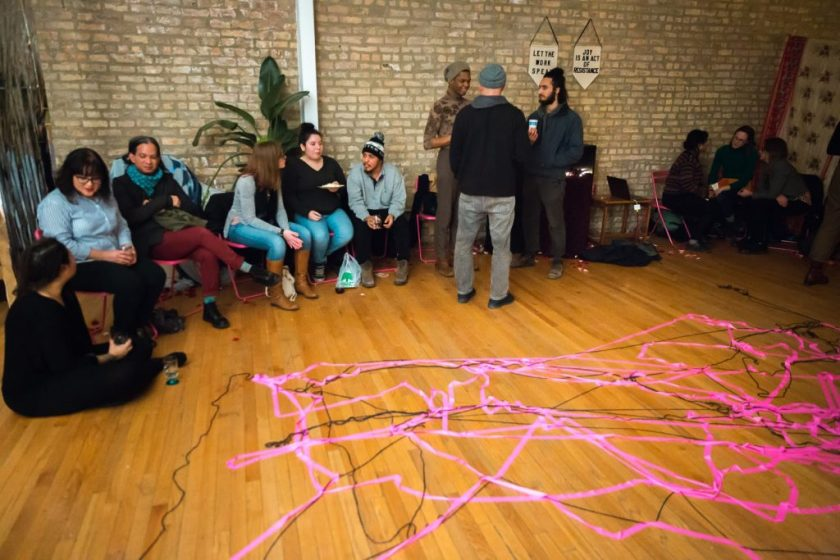 "Image: In-Session, at Threewalls in March 2019, by Maya Mackrandilal with collaborators Udita Upadhyaya and Enid Muñoz and original performance for video by Bhanu Kapil, in response to the guiding work ""Schizophrene"" by Bhanu Kapil. In the background of this shot, trios of audience members and performers sit or stand around the room, chatting after the performance and discussion. Remnants of the performance are in the foreground — a layered web of pink fluorescent ribbon and black string on the wood floor, reflecting where many audience members stood during one part of the performance. Many audience members wear hats, sweaters, or other cold-weather clothes. Photo by Milo Bosh. Courtesy of Threewalls."