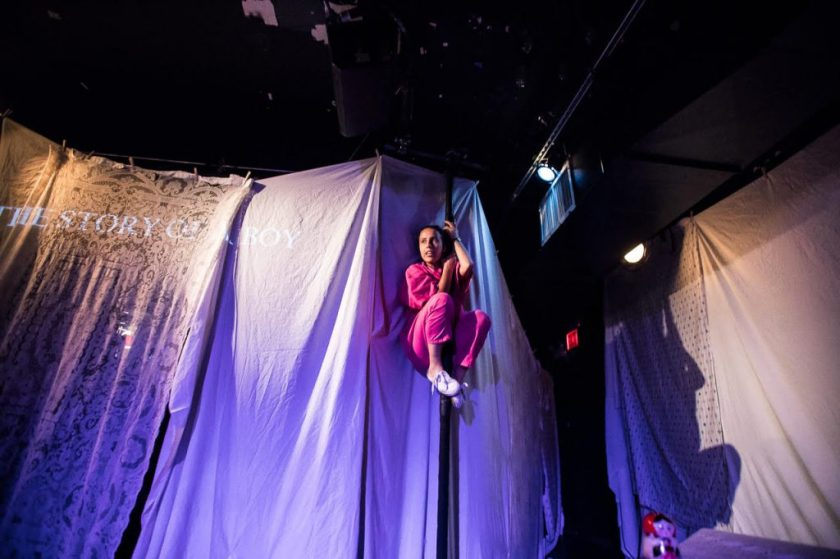 """Image: Center, Ida holding herself in a crouch position on a pole in front of a wall of curtains. To the left at level with Ida's head, projected across a taffeta sheet and a bedsheet are the words """"THE STORY OF A BOY."""" To the right, the sheets taper off into a hall and at the top, a red exit sign. Further right, Ida's shadow on the wall. Below that on top of a box, a Russian nesting doll. Photo Courtesy of Brave Lux, Inc."""