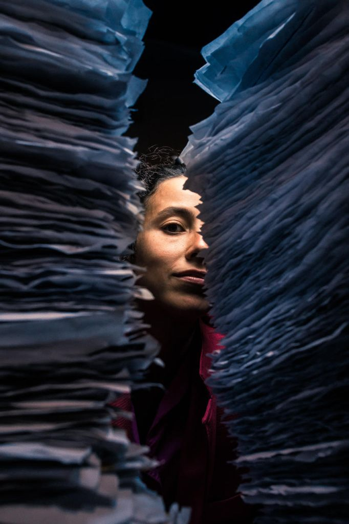 Image: Two stacks of wrinkled, fringed, blue-tinted papers stand close to the camera, blurred. Between them, Ida Cuttler looks at the camera with an almost-smile; the right side of her face is obscured by the stack of paper. Above and below her face is darkness. She wears a pink blazer. Photo courtesy of Brave Lux, Inc.