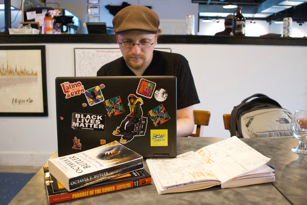 "Image: Damian Duffy sits at a table in a brewery and works at a laptop computer. In front of his computer are paperback copies of Octavia Butler's ""Parable of the Talents"", an advanced reader copy of his graphic novel adaptation of Butler's ""Parable of the Sower"", and an open notebook with sketches. An empty beer glass is set to the side. Photo by Jessica Hammie."