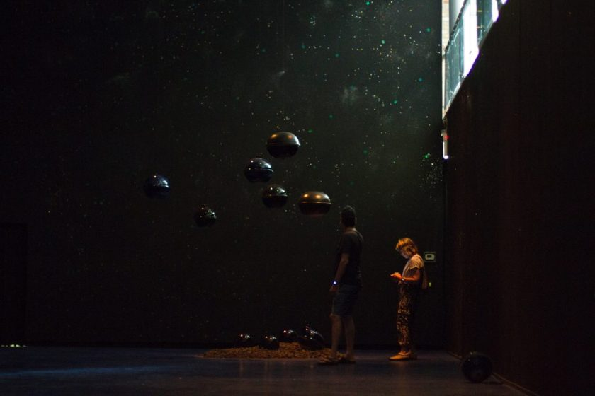 """Image: Viewers interacting with """"Dark Matter: Celestial Objects as Messengers of Love in These Troubled Times"""" by Folayemi Wilson at the Hyde Park Art Center. The installation has made the space very dark with hanging orbs towards the middle of the frame. Photo by Michael Sullivan."""