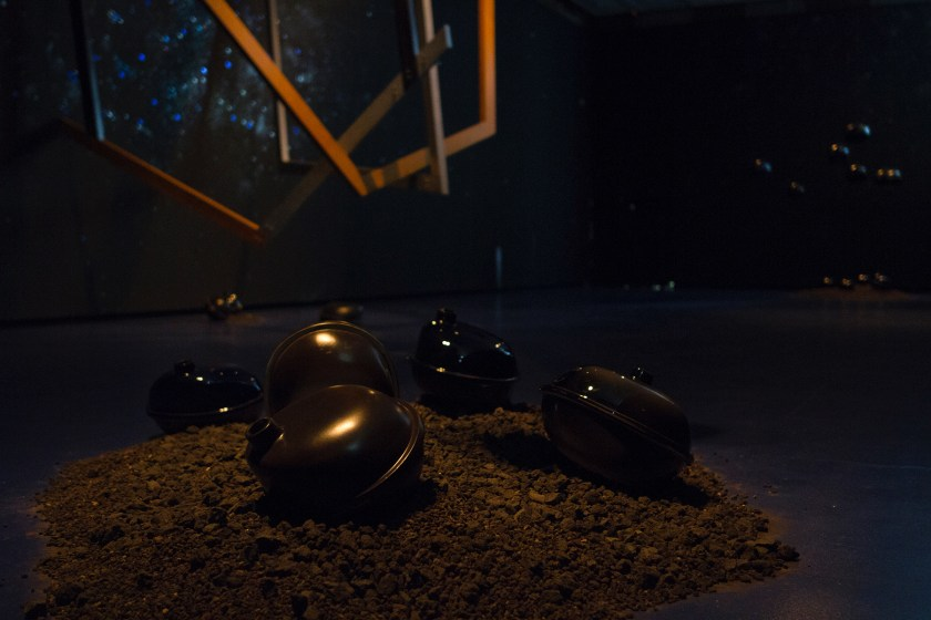 """Image: 'Fallen objects' from outer space within the installation """"Dark Matter: Celestial Objects as Messengers of Love in These Troubled Times"""" by Folayemi Wilson at the Hyde Park Art Center. Dirt lay on the floor with sculptural objects on and suspended above. Photo by Michael Sullivan."""
