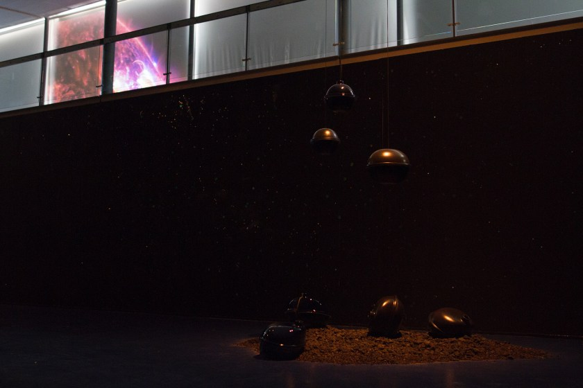 """Image: Installation view of """"Dark Matter: Celestial Objects as Messengers of Love in These Troubled Times"""" by Folayemi Wilson at the Hyde Park Art Center. Objects are hanging in the air and 'crash landing' onto a pile of earth. Photo by Michael Sullivan."""