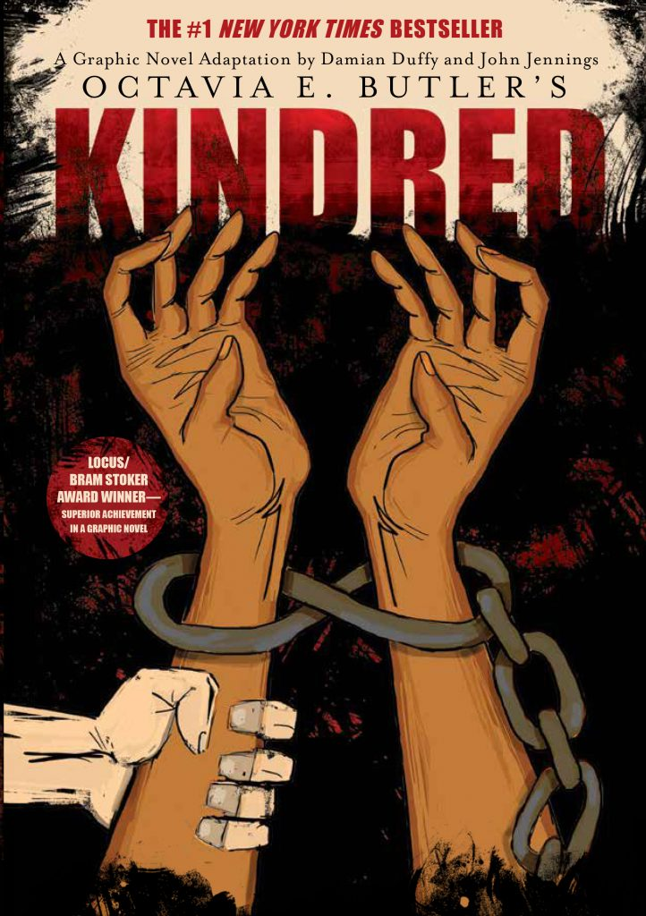 """Image: The cover of """"Kindred: A Graphic Novel Adaptation"""" features two brown arms reaching upward, with chains around the wrists against a black and red backdrop. A white hand grabs the left arm. Image courtesy of Damian Duffy."""