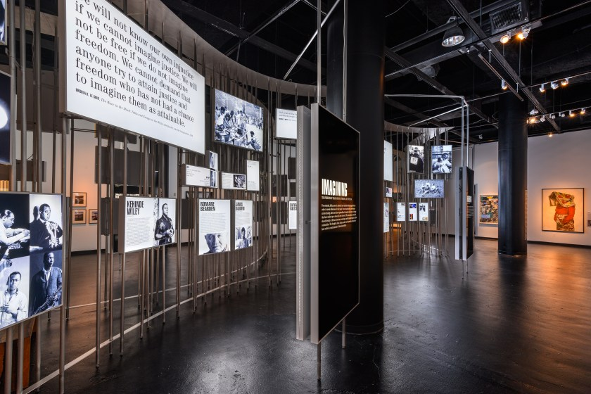 Installation view of Men of Change. The installation made of metal poles is in the middle of the room. Light boxes of various sizes featuring photos and text are hung on the metal poles. A large display box in front of the installation features a poster that reads STORYTELLERS. Along the walls of the room are paintings and other artworks, most of which are obscured by the metal pole installation in the middle of the room. A woman stands in front of the light box installation, looking at the installation. Photo by Phil Armstrong. Photo courtesy of the Smithsonian Institution Traveling Exhibition Service.