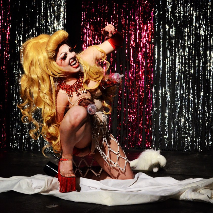 Image: The performer is on one knee as they are in mid-performance. They are wearing red platform shoes, fetish wear, breast pumps, and a red necklace. They have a large blonde wig on and their mouth is open. Behind them are colorful tinsel.  Photo by M T Daniel.