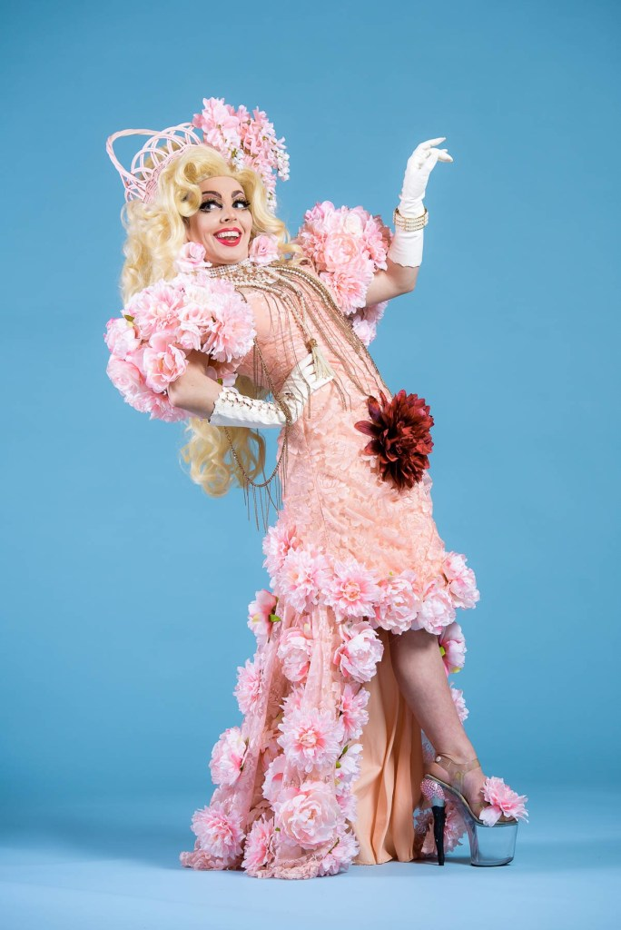 Image: The background is light blue and the figure is standing in the center of the frame. The costume is elaborate with various large flowers on the bottom of a pink dress and on the sleeves. The performer's shoes are see-through platform heels with a large pink flower on them. The performer is wearing a long, blonde wig. They have their back slightly arched and are looking off towards the left side of the camera. Photo by Jason Brown [@cjasonbrown].