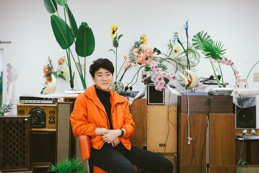 Rachel Youn in their studio. They sit in front of untitled works comprised of massagers, artificial plants, and speaker cabinets. Photo by Krista Valdez.