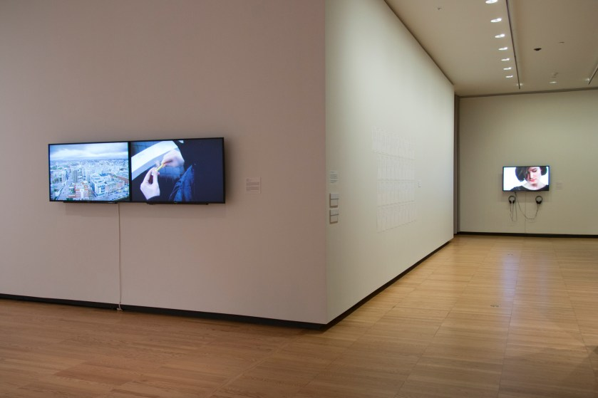 "Image: ""Kennedy Browne: The Special Relationship,"" installation at Krannert Art Museum, University of Illinois at Urbana-Champaign, 2018. On the left, a two-channel video artwork hangs on the wall. There are two screens pushed together. On the right, there is an installation of paper on the wall, and another video artwork on one screen, below which are two sets of headphones. Courtesy of Krannert Art Museum. Photo by Julia Nucci Kelly."
