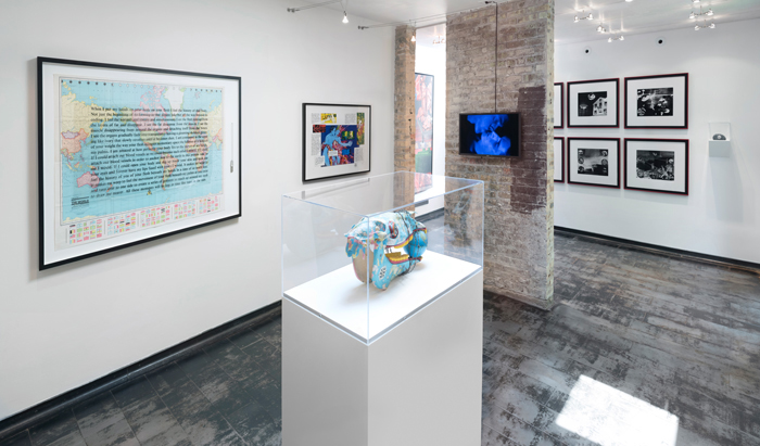 "Image: Installation shot of Iceberg Projects exhibition ""David Wojnarowicz: Flesh of My Flesh,"" June 23 – August 5, 2018. In the middle of the room, a sculpture sits on a white pedestal, encased in glass. A world map with words overlaying the image is hanging on the wall to the left, and a video screen is displaying a video on the partial brick wall directly in front of the viewer. Image courtesy of Iceberg Projects."