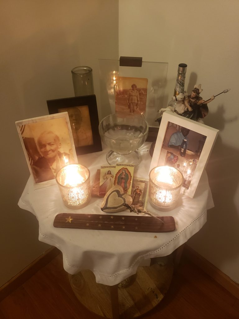 Image: Mario LaMothe's altar in his home. The altar consists of multiple framed photographs of LaMothe's family members sitting on a table with a white tablecloth. Candles and incense accompany the photographs. Photo courtesy of Mario LaMothe.