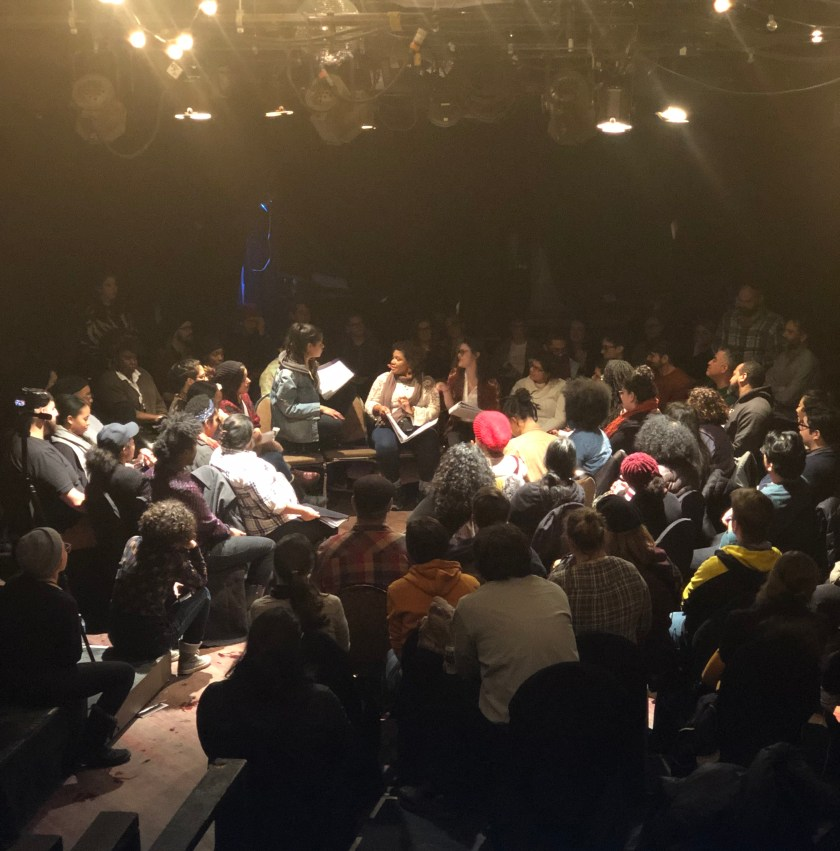 "Image: A live reading of Tanuja Devi Jagernauth's play, ""How to Pick a Lock,"" at Prop Thtr in 2019. In the center, a seated performer speaks to a performer who is crouched on a chair; other performers sit near them. All hold scripts. An audience of dozens encircles them. Stage lights and stringed lights hang from the ceiling. Photo by Tara Branham."