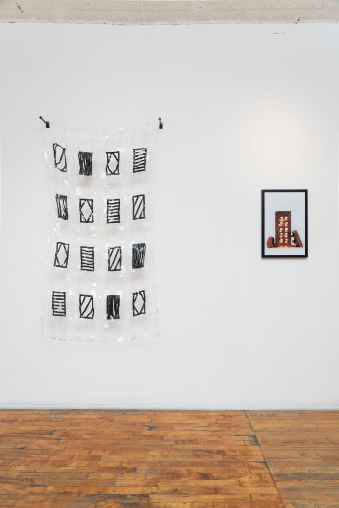 Image: A straight forward look at a white gallery wall with the wood floor on the lower half of the image. The left piece, titled Clueless by Rebecca Griffith, is a quilt that hangs from the wall with 16 black rectangular shapes and clear tape. To the right is the piece When the Dust Settles by Elyse Sawka, which features a framed photograph of a brick. Photo by Jesse Meredith.