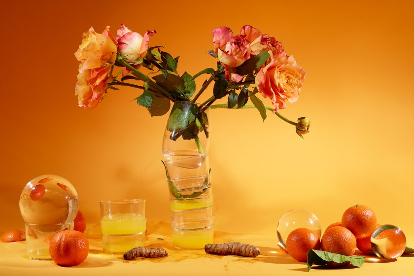 Featured image: The Six, 2020 by Marzena Abrahamik. A photograph of a still life of a orange and red bouquet of flowers on an orange-yellow table. On the table also sits oranges and various plant parts. The background dis also orange-yellow. Image courtesy of the artist.