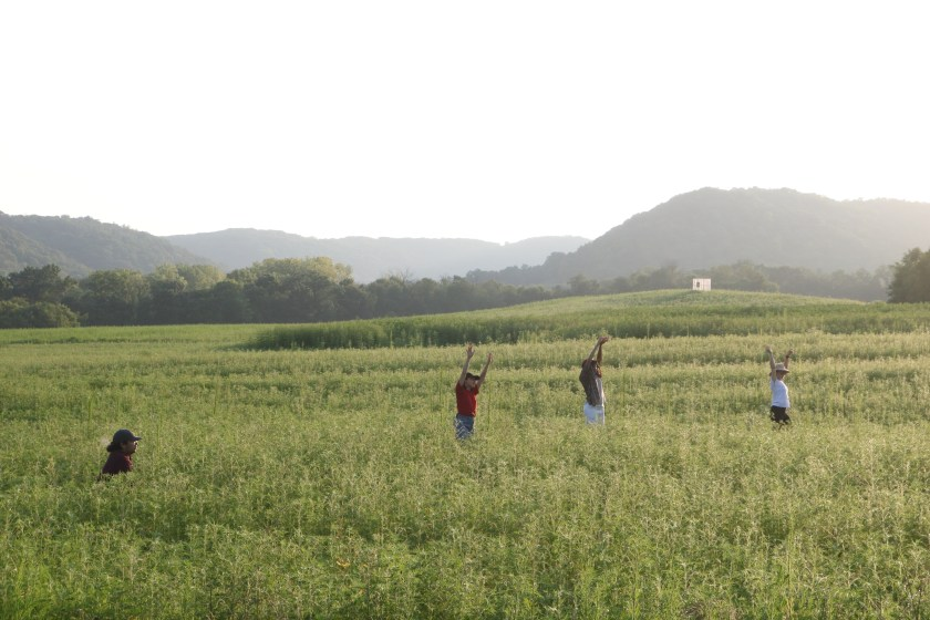 Image: ACRE residents stand in a green valley surrounded by hills in rural Wisconsin. Three of the people in the field are standing with their hands raised above their heads, and the person to the left is crouching towards the ground. Photo by Zachary Hutchinson, courtesy of ACRE.