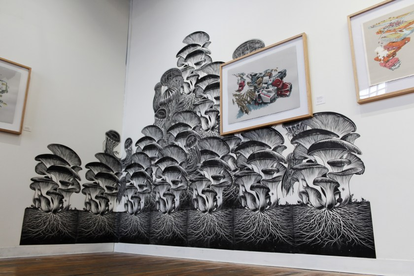 Image: Emmy Lingscheit, Remediators, wheat-pasted print installation at Spudnik Gallery, 2018. Black and white linocuts of mushrooms and jellyfish are collaged together to create one large heap, in the corner of an exhibition gallery. The heap is triangular in shape, with the apex in the center of the photograph. There are roots growing underneath the mushrooms, and these roots resemble the tentacles of the jellyfish. There are some small fish that are swimming in between the jellyfish tentacles. There are other framed prints hung on the wall. One framed print is installed over the installation. Image courtesy of Emmy Lingscheit.