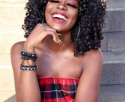 happy trendy black woman sitting on stairs and laughing