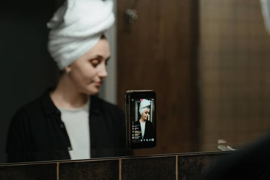 man in white knit cap holding black smartphone