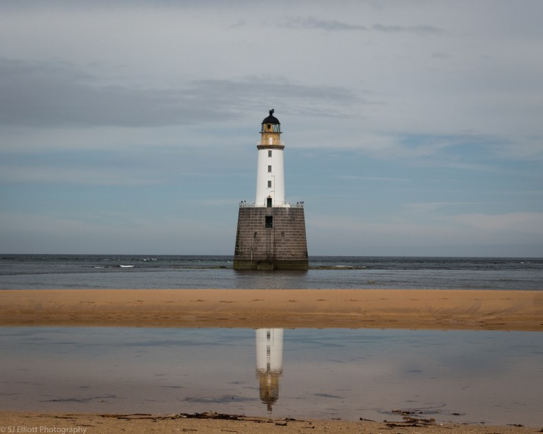 Rattray Head Lighthouse reflecting off pools on the beach.