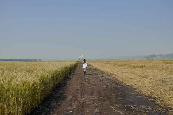 female in white dress walking along road in field