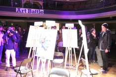 The audience waits around the four final pieces as the judges tally the votes