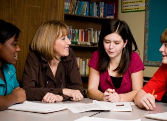 Teacher speaking to three students sitting at a desk. Two students are holding pencils.