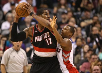 A basket ball player trying to block another player who is holding the ball in the air.