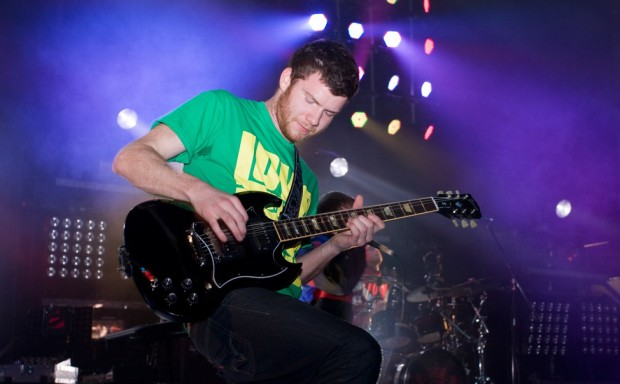 A man in a green and yellow tee shirt playing a black guitar.