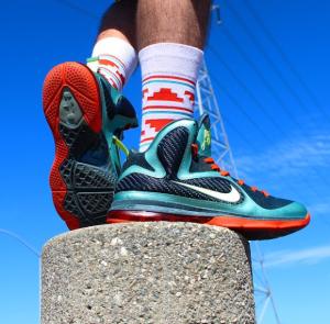 Someone wearing white and orange socks wearing orange, blue and white Nike shoes.