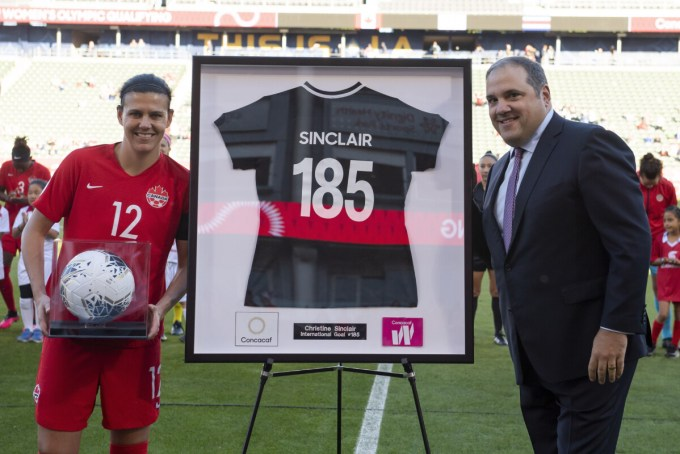 Christine Sinclair is presented with the game ball and a commemorative jersey for breaking the world's all-time international goalscoring record