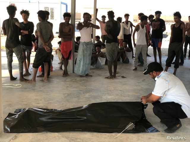 Migrants watch the body of their fellow migrant who died after a wooden boat capsized off the coast of Komas, a town east of the capital Tripoli, Libya, July 25, 2019.