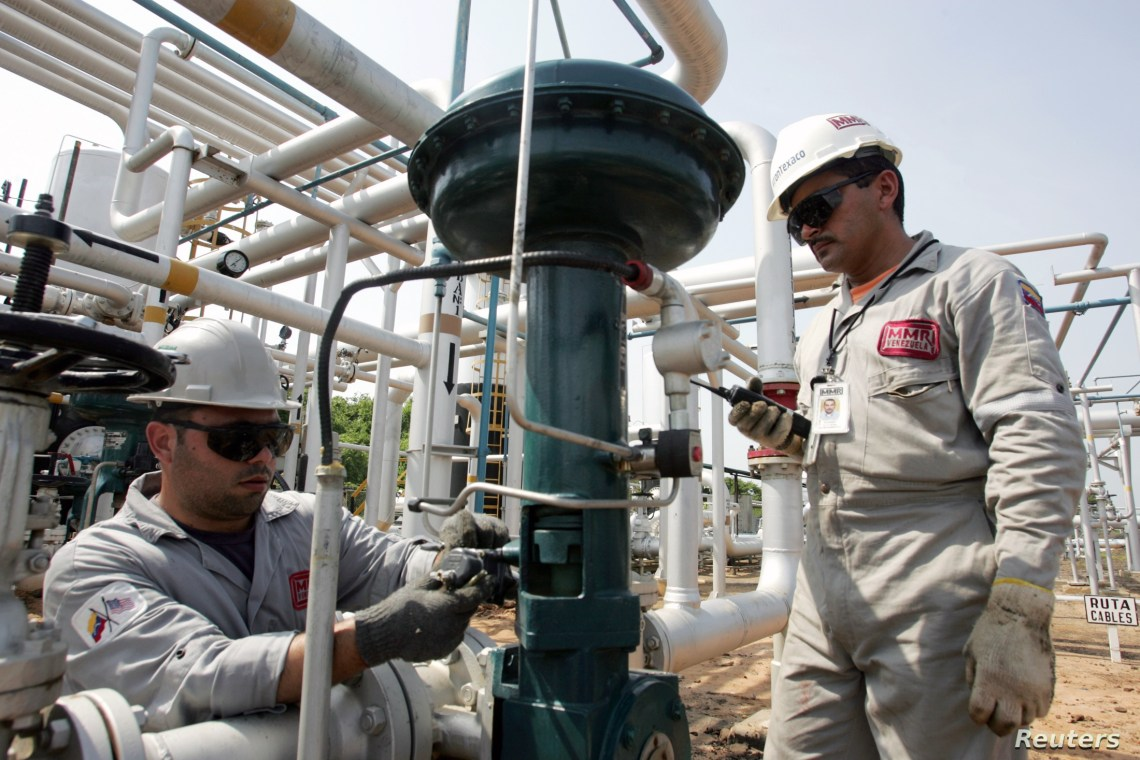FILE - Oil workers conduct routine maintenance on a gas plant at field Boscan, operated under a joint venture model between Venezuelan state oil company PDVSA and U.S. Chevron, outside Maracaibo City in Venezuela, May 26, 2006.