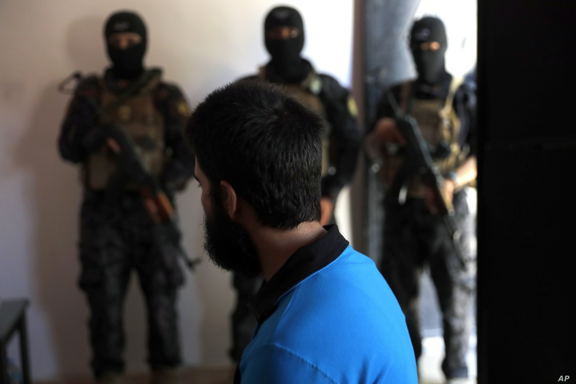 FILE - In this picture taken July 21, 2017, Kurdish soldiers from the Anti-Terrorism Units, background, stand in front a blindfolded suspected Islamic State member from Turkey at a security center, in Kobani, Syria.