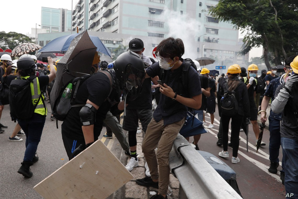 Protesters react as tear gas is released by police during a faceoff at the entrance to a village at Yuen Long district in Hong Kong, July 27, 2019.