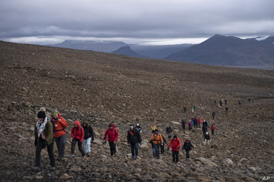 People climb to the top of what once was the Okjokull glacier, in Iceland, Aug. 18, 2019.