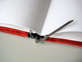 Die Roter-Faden-Mechanik mit den aufklappbaren Papierhaltehaken.