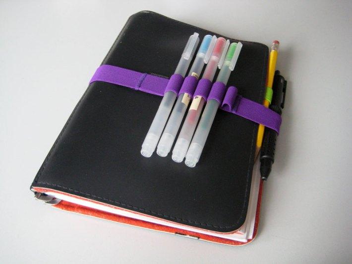 Roter Faden Taschenbegleiter. Meine Original-Gummizuglasche war nach Jahren kaputt; ich habe sie durch einen anderen Hummizug-Stifthalter ersetzt.