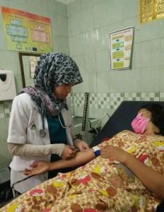 Tenaga kesehatan Rumah Sehat Amira, Vonil Vila Delviza saat sedang melakukan pemeriksaan terhadap pasien