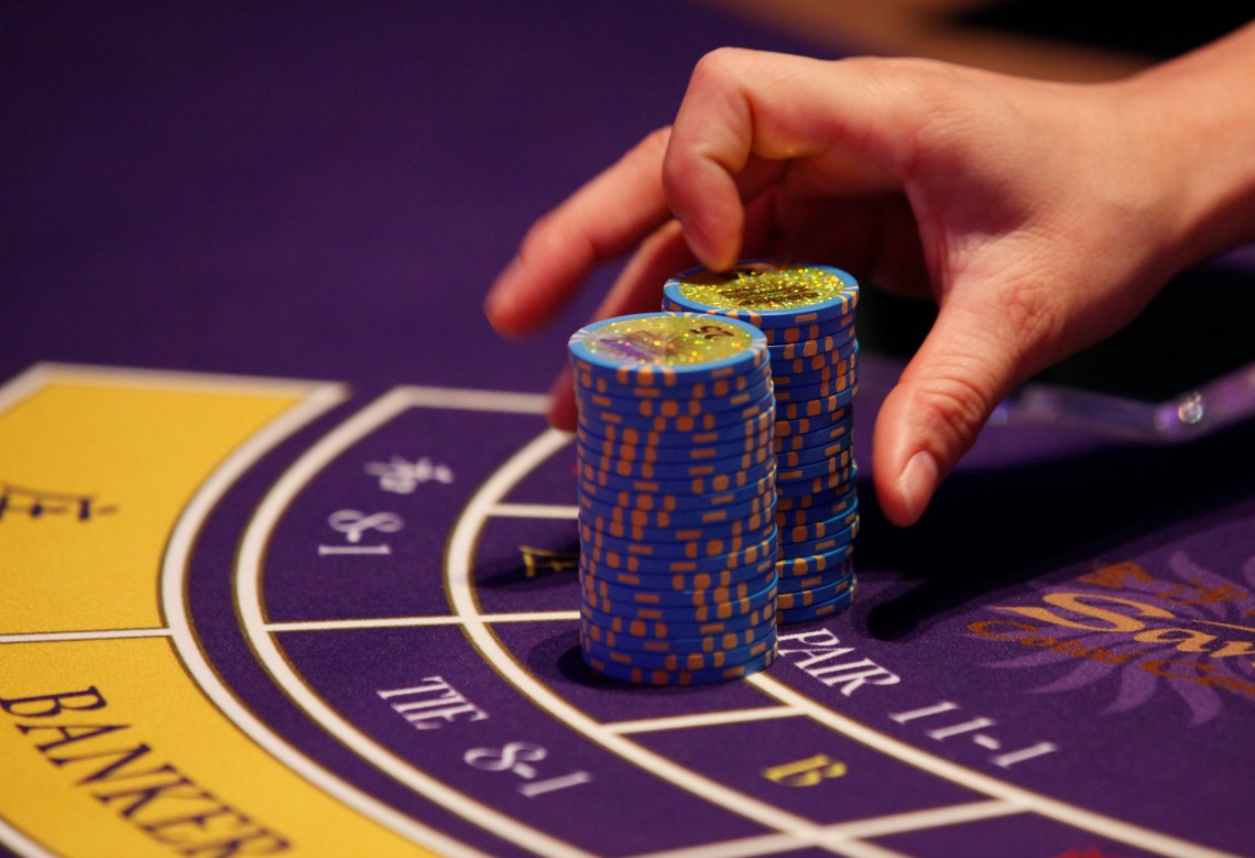 FILE - a croupier counts the chips at a baccarat gaming table inside a casino during the opening day of Sheraton Macao Hotel at the Sands Cotai Central in Macau.