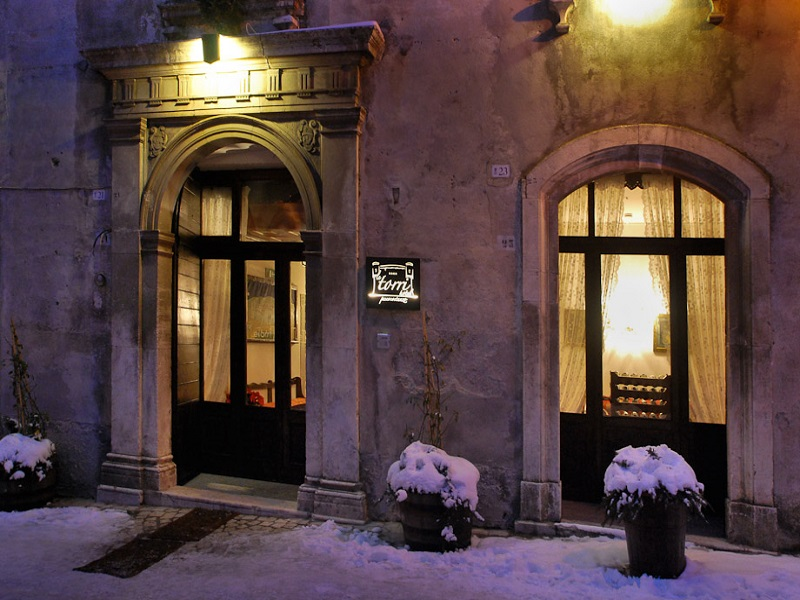 Exterior shot with illuminated entrance and snow on the ground