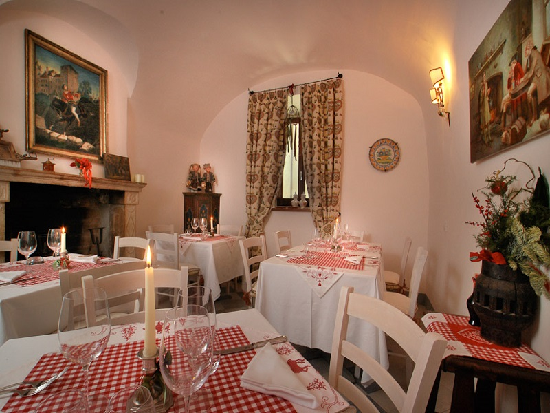 The restaurant with fireplace and tables laid with tablecloths and candles