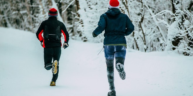 Two male athlete running on winter alley in Park