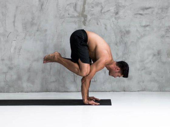 man doing crow pose