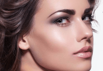 a beautiful model turns and faces the camera showing off her clear skin