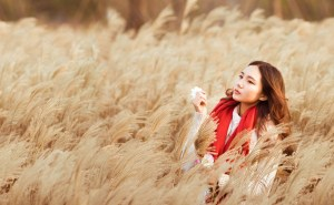 girl with a red scarf stands in a wheat field