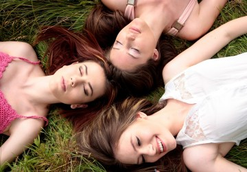 three women lay in the grass and smile