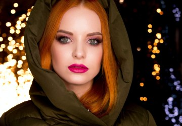stunning woman wears a hood and stares at the camera