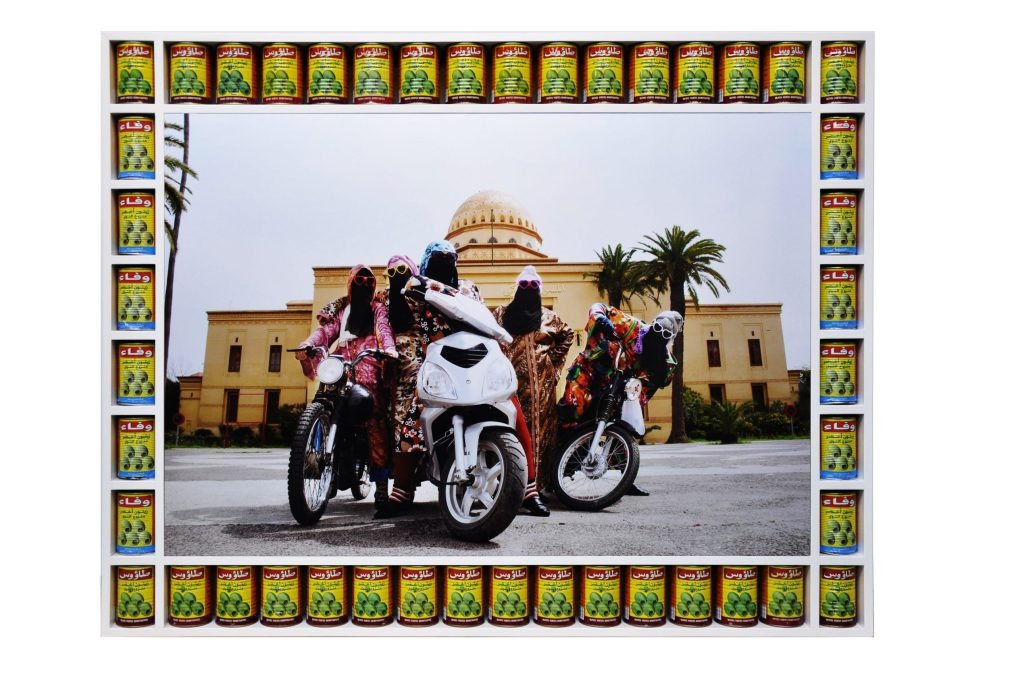 An image of artwork Kesh Angels by Hassan Hajjaj, a photograph of five Black figures wearing colourful clothing and sunglasses on motorbikes and mopeds. Around the edge of the photograph, tins of olives sit in a white frame.