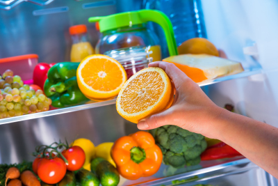 woman getting orange from the fridge